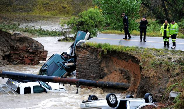 "Officials investigate the scene of a road collapse at Highway 287 and Dillon at the Broomfield/Lafayette border, Colo., that sent three vehicles into the water after flash flooding on Thursday, Sept. 12, 2013. The National Weather Service has warned of an ""extremely dangerous and life-threatening situation"" throughout the region. (AP Photo/Daily Camera, Cliff Grassmick)"