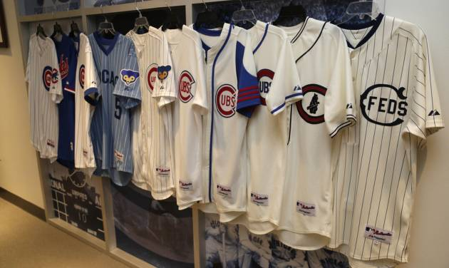 In this March 24, 2014, photo Chicago Cubs and the Chicago Feds jerseys worn over the past 100 years at Wrigley Field are on display at the Cubs offices in Chicago. The season long celebration of the 100th anniversary of the iconic ballpark begins with a visit from an old friend. Former Cubs first baseman Ryne Sandberg, now a manager, brings his Philadelphia Phillies to take on the Cubs in a baseball game on on opening day, Friday April 4, 2014 in Chicago. (AP Photo/M. Spencer Green)