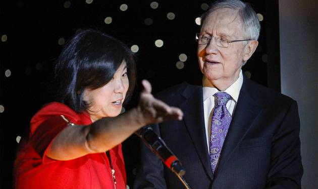 In this photo taken on Thursday, Aug. 21, 2014, U.S. Rep. Grace Meng, D-Queens,  and U.S. Sen. Harry Reid, D-Nev., take the stage during the Asian Chamber of Commerce's monthly lunch at the Gold Coast casino-hotel in Las Vegas. Reid, the Democratic Senate Majority Leader, apologized Friday, for jokes he made about Asians during the luncheon. (AP Photo/Las Vegas Review-Journal, Erik Verduzco) LAS VEGAS SUN OUT