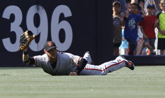 San Francisco Giants center fielder Gregor Blanco makes a diving catch on a line drive by San Diego Padres' Will Venable during the first  inning of a baseball game Saturday, July 5, 2014, in San Diego. (AP Photo/Don Boomer)
