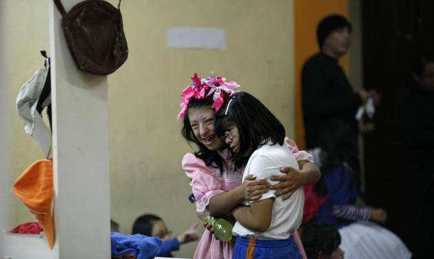 """In this Sept. 21, 2012 photo, two actresses embrace in a backstage dressing room prior to their performance in """"Suenos,"""" or """"Dreams,"""" one of Ecuador's most successful musicals, at the Casa de la Cultura theater in Quito, Ecuador. The musical is based in part on the dreams of young people with disabilities and is presented by the nonprofit foundation El Triangulo. (AP Photo/Dolores Ochoa)"""