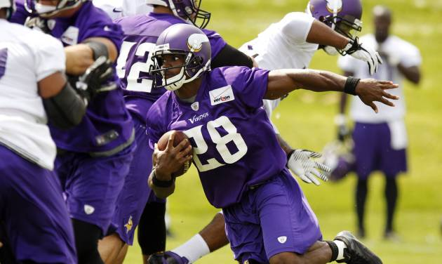 In this photo taken June 18, 2013, Minnesota Vikings running back Adrian Peterson carries the ball during NFL football minicamp at Winter Park in Eden Prairie, Minn. In training camp, an allergic reaction to shellfish caused Peterson to gasp for air as his throat swelled. Vikings staff had epinephrine injections handy, and the star running back was soon out of trouble. Now, Peterson has added EpiPen to his portfolio of sponsorships, grateful for the safety net it provides. (AP Photo/Genevieve Ross)
