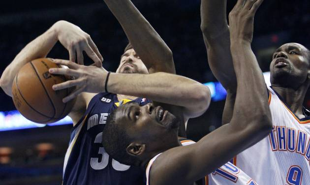 Memphis Grizzlies center Marc Gasol, left, wraps up Oklahoma City Thunder forward Kevin Durant, center, as he grabs a rebound in the second quarter of an NBA basketball game in Oklahoma City, Wednesday, Nov. 14, 2012. Oklahoma City Thunder forward Serge Ibaka (9) is at right. (AP Photo/Sue Ogrocki)