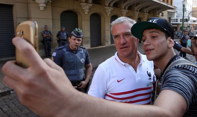 France head coach Didier Deschamps poses for a selfie with a fan before the start of Deschamps' press conference at the Teatro Pedro II, in Ribeirao Preto, Brazil, Friday, July 1, 2014. France will face Germany in their World Cup quarterfinal, Friday. (AP Photo/David Vincent)
