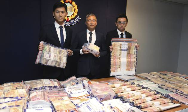 In this June 9, 2014 photo, officers from Hong Kong Police's organized crime and triad bureau, display stacks of cash seized after they launched an operation with counterparts in mainland China to smash a cross-border illegal gambling syndicate days before the start of the World Cup in Brazil. As teams battle for glory at football's biggest event, the biggest winners may be Asia's illegal bookmakers, who are thriving because demand from sports fans to place bets is surging but legal options are few. Government monopoly operators offer legal sports betting in a handful of Asian jurisdictions but there are thousands more black market operators. Asia accounts for just over half of the nearly $700 billion in illegal bets placed worldwide each year, according to a sports monitoring group.  (AP Photo)