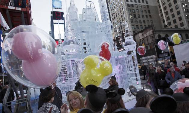 """People with mouse ear caps and balloons gather near a three-story castle mad of ice in New York's Times Square, Wednesday, Oct. 17, 2012. On Wednesday, Disney announced a new program for 2013, """"Limited Time Magic,"""" in which guests will encounter surprise weekly themes at Disney parks in Florida and California. The program was described as """"52 weeks of magical experiences big and small that appear, then disappear as the next special surprise debuts."""" For example, a weeklong Valentine's Day celebration might include pink lighting on Disney castles, surprise meet-and-greets with Disney characters and candlelit dinners for lovebirds. (AP Photo/Richard Drew)"""