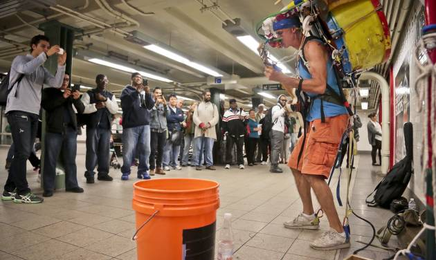 """In this Wednesday, Oct. 9, 2013, photo, subway riders pause to listen as Jeffrey Masin, right, performs his one-man band ensemble at a subway platform at Union Square station in New York. Masin, from Waterford, Conn., has performed his one-man band show he calls """"Jumping Jam Band"""" since 1979, traveling across the U.S. and Europe.  A street musician mostly, he started performing legally  at subway stations more than a year ago and it's been """"very good.""""  (AP Photo/Bebeto Matthews)"""
