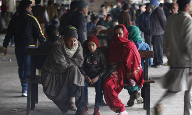 Stranded passengers sit at a bus station as they wait for the reopening of the Jammu-Srinagar highway in Jammu, India, Thursday, Feb. 11, 2016. Following continued snowfall, the Jammu-Srinagar highway, that connects the Kashmir valley to the rest of India, was closed to traffic, news reports said. (AP Photo/Channi Anand)