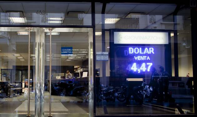 A sign shows the official government-set exchange rate of 4.47 Argentine pesos per 1 U.S. dollar at a money exchange house in Buenos Aires, Argentina, Wednesday, May 16, 2012. The AFIP tax collection agency recent measure to control and approve every currency exchange operation in the country has made practically impossible for Argentines to buy dollars, forcing them to get the currency on the black market. (AP Photo/Natacha Pisarenko)