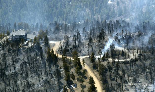 FILE - In this March 27, 2012 photo, one home stands untouched at left while another home at right smolders after burning in the Lower North Fork Wildfire in the foothills community of Conifer, Colo., southwest of Denver. Emergency officials told confused residents not to worry after they reported a fire on the outskirts of Denver, including at least two residents who later were found dead in their burning home, 911 calls released by officials Tuesday showed. (AP Photo/David Zalubowski, File)
