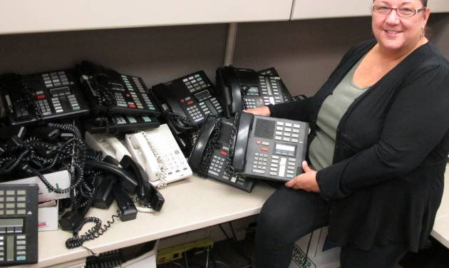 In this Monday, Sept. 17, 2012 photo, Mary Morgan, a Nassau County information technology specialist, poses with the telephones she is assessing as part of a countywide efficiency effort in Mineola, N.Y. Nassau County is currently shutting off hundreds of unused telephone lines and reviewing their current stock of telephones as part of a cost-cutting initiative. (AP Photo/Frank Eltman)