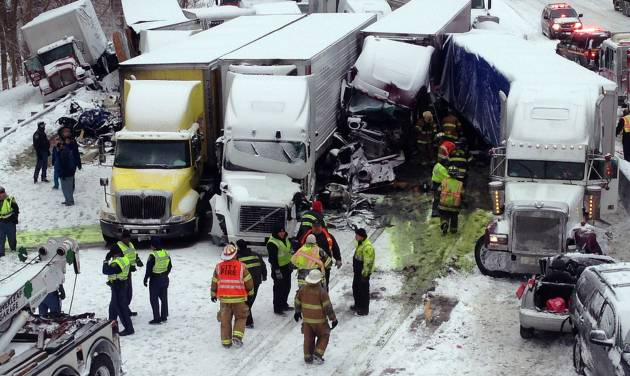 In this photo provided by the Indiana State Police, emergency crews work at the scene of a massive pileup involving more than 40 vehicles, many of them semitrailers, along Interstate 94, Thursday afternoon, Jan. 23, 2014, near Michigan City, Ind. At least three were killed and more than 20 people were injured. (AP Photo/Indiana State Police)