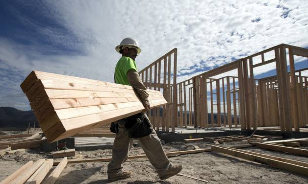 In this Friday, Nov. 16, 2012, photo, construction worker Miguel Fonseca carries lumber as he works on a house frame for a new home  in Chula Vista, Calif. Confidence among U.S. homebuilders inched up in Novemeber to the highest level in more than six and a half years, as builders reported the best market for newly built homes since the housing boom.(AP Photo/Gregory Bull)