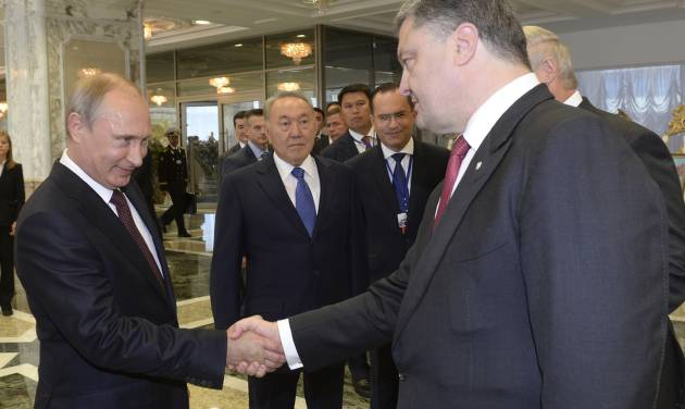Russian President Vladimir Putin, left, shakes hands with Ukrainian President Petro Poroshenko, right, as Kazakh President Nursultan Nazarbayev, center, looks at them, prior to their talks after after posing for a photo in Minsk, Belarus, Tuesday, Aug. 26, 2014. Leaders of Russia, Belarus, two other former Soviet republics as well as top EU officials are meeting in Minsk, Belarus, for a highly anticipated summit to discuss the crisis in Ukraine which has left more than 2,000 dead and displaced over 300,000 people. (AP Photo/Kazakh Presidential Press Service, Sergei Bondarenko, Pool)
