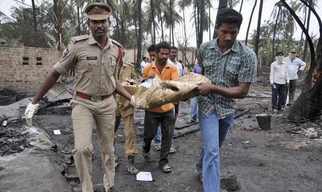Indian police officers and rescue workers carry the body of a pipeline blast victim in Nagaram village, India, Friday, June 27, 2014. A state-owned gas pipeline exploded and burst into flames Friday, killing at least 15 people, destroying homes and forcing the evacuation of neighboring villages in the southern Indian state of Andhra Pradesh, authorities said. (AP Photo)