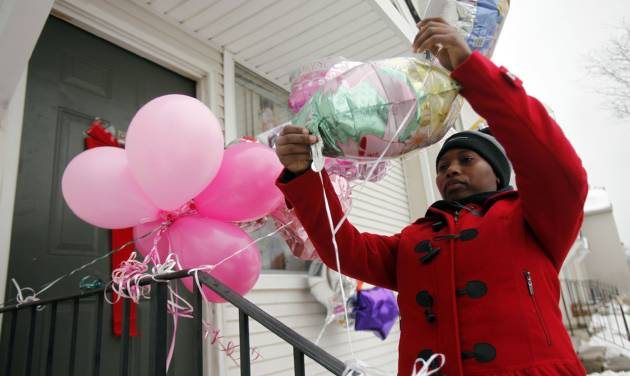 In this photo taken Monday, Dec. 31, 2012, Dornecia Helms, of Detroit places up balloons on the door step of an eight year-old stabbing victim Tameria Greene at the Martin Luther King Apartments, in Detroit. Semeria Greene was charged Wednesday with felony murder in the stabbing death of her daughter Tameria Greene, at their Detroit home just days before the girl's 9th birthday. (AP Photo/Detroit Free Press, Andre J. Jackson)  DETROIT NEWS OUT; NO SALES; INTERNET OUT; MAGS OUT; TV OUT; MANDATORY CREDIT