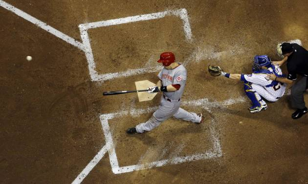 Cincinnati Reds' Todd Frazier hits an RBI single during the fifth inning of a baseball game against the Milwaukee Brewers Friday, June 13, 2014, in Milwaukee. (AP Photo/Morry Gash)