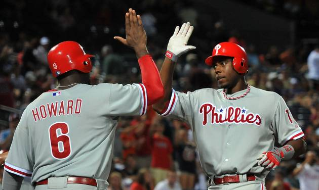 Philadelphia Phillies' John Mayberry (15) celebrates his three-run home run against the Atlanta Braves at the plate with teammate Ryan Howard (6) during the tenth inning of a baseball game on Friday, Aug. 31, 2012, at Turner Field in Atlanta. (AP Photo/Gregory Smith)