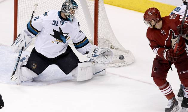 San Jose Sharks' Antti Niemi (31), of Finland, makes a save on a shot as Phoenix Coyotes' Martin Erat, right, of the Czech Republic, watches during the third period of an NHL hockey game on Saturday, April 12, 2014, in Glendale, Ariz. The Sharks defeated the Coyotes 3-2. (AP Photo/Ross D. Franklin)