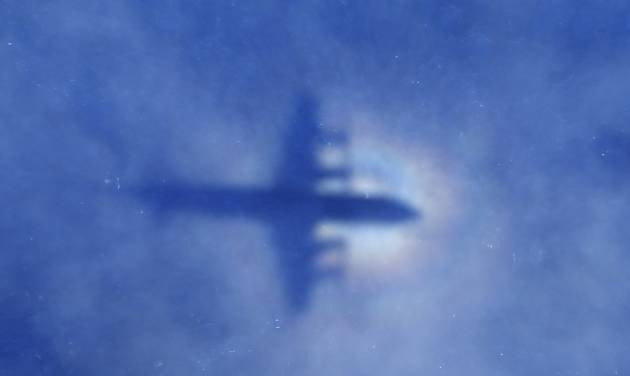 In this Monday, March 31, 2014 photo, a shadow of a Royal New Zealand Air Force P-3 Orion aircraft is seen on low cloud cover while it searches for missing Malaysia Airlines Flight MH370 in the southern Indian Ocean. Malaysia's national police chief has warned that the investigation into what happened to the plane may take a long time and may never determine the cause of the tragedy. Khalid Abu Bakar said Wednesday, April 2, that the criminal investigation is still focused on four areas — hijacking, sabotage and personal or psychologica problems of those on board the plane. (AP Photo/Rob Griffith, Pool)