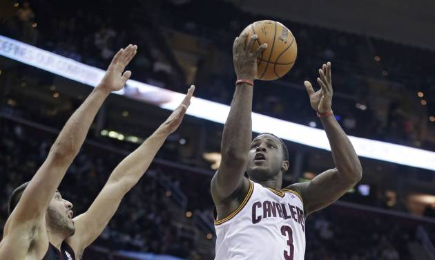 Cleveland Cavaliers' Dion Waiters (3) jumps to the basket between Toronto Raptors' Greivis Vasquez (21) and Chuck Hayes (44) during the fourth quarter of an NBA basketball game Tuesday, March 25, 2014, in Cleveland. Waiters scored a team-high 24 points for Cleveland's 102-100 win.(AP Photo/Tony Dejak)