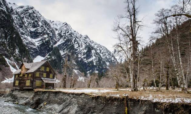 FILE - In this April 2014, file photo provided by Olympic National Park, the Enchanted Valley Chalet stands on the eroding bank of the Quinault River in Olympic National Park in Washington state. The park says it is moving forward with a plan to move the chalet that is being threatened by the shifting east fork of the river. (AP Photo/Olympic National Park, File)