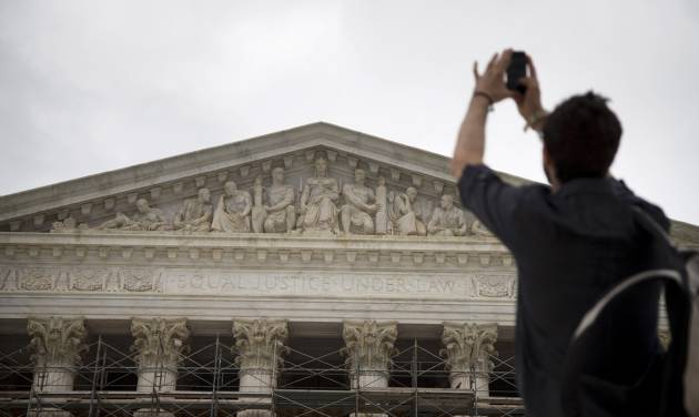 Chris Sharp of Brooklyn, N.Y., takes a photo of the Supreme Court in Washington, Monday, Oct. 7, 2013, as he waits in line for the beginning of the 2013-2014 opening term. The justices take the bench Monday for the start of their new term with important cases about campaign contributions, housing discrimination and government-sanctioned prayer already on tap. Abortion, contraceptive coverage under the president's new health care law and mobile phone privacy also may find their way onto the court's calendar. (AP Photo/ Evan Vucci)