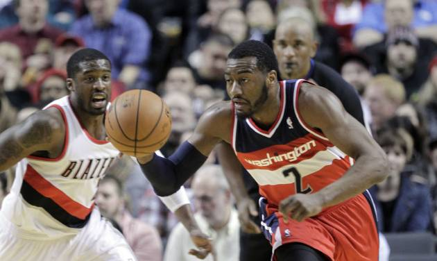 Washington Wizards guard John Wall, right, races down court after stealing the ball from Portland Trail Blazers guard Wesley Matthews, left, during the first half of an NBA basketball game in Portland, Ore., Thursday, March 20, 2014. (AP Photo/Don Ryan)