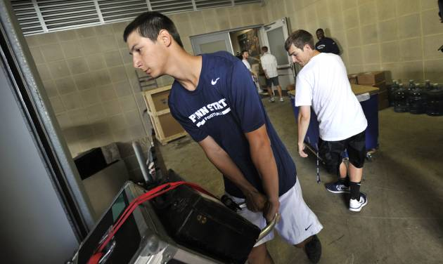 Penn State team managers Nick Venturino, left, and Evan Tucker, right, load equipment to be shipped to Ireland, in University Park, Pa., Tuesday, Aug. 26, 2014.  Penn State plays Central Florida in the Croke Park Classic, in Dublin, Ireland, this Saturday.     (AP Photo/Centre Daily Times,Nabil K. Mark    MANDATORY CREDIT; MAGS OUT