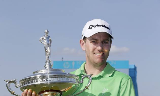Brendon Todd holds up the trophy after winning the Byron Nelson Championship golf tournament, Sunday, May 18, 2014, in Irving, Texas. Todd finished the tourney at 14-under par, two strokes ahead of Mike Weir who finished second. (AP Photo/Tony Gutierrez)