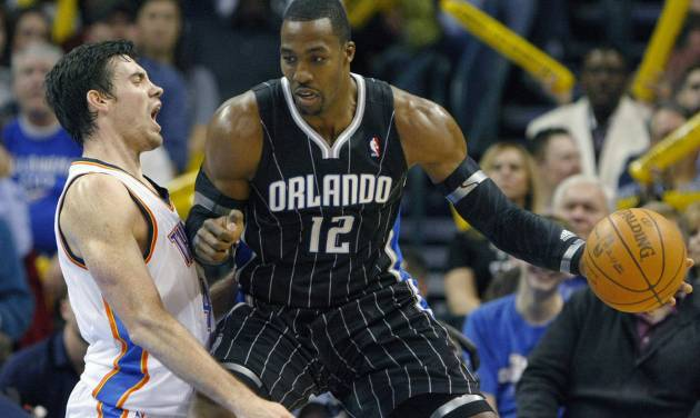 Orlando Magic's Dwight Howard (12) drives to the basket against Oklahoma City Thunder's Nick Collison, left, during the third quarter of an NBA basketball game in Oklahoma City, Sunday, Dec. 25, 2011. The Thunder won 97-89. (AP Photo/Alonzo Adams) ORG XMIT: OKAA110