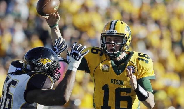 FILE - IN this Jan. 4, 2014 file photo, North Dakota State quarterback Brock Jensen gets a pass off under pressure from Towson defensive end Ryan Delaire during the FCS championship NCAA college football game  in Frisco, Texas. NDSU won 35-7. Jensen, who is the winningest quarterback in NCAA Football Championship Subdivision history, is gearing up for his pro day in Fargo on Wednesday, March 12, 2014, after being overlooked for the NFL combine. (AP Photo/Tony Gutierrez, File)