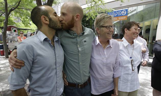 From left, Moudi Sbeity and Derek Kitchen kiss accompanied by fellow plaintiffs Laurie Wood and Kody Partridge at a news conference outside their lawyer's office in Salt Lake City on Wednesday, June 25, 2014. On Wednesday, a federal appeals court in Denver ruled that states must allow gay couples to marry, finding the Constitution protects same-sex relationships. The decision from a three-judge panel in Denver upheld a lower court ruling that struck down Utah's gay marriage ban which the couples fought. (AP Photo/Rick Bowmer)