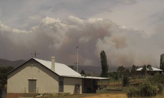 Wildfire smoke rises from hills behind the village of Numeralla in New South Wales state on Tuesday, Jan. 8, 2013. Wildfires raged across much of southeast Australia. (AP Photo/Rod McGuirk)