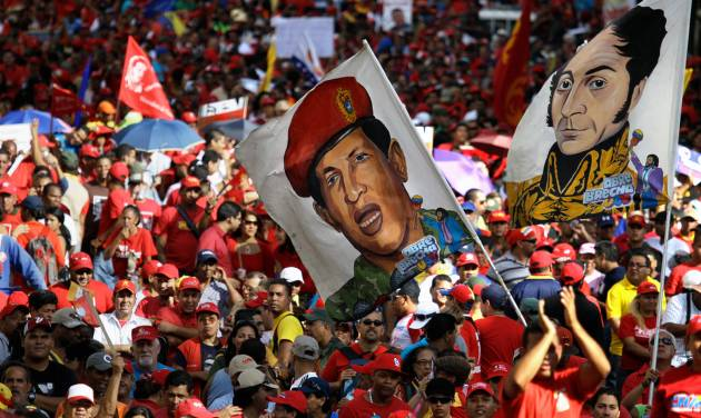 FILE - In this Jan. 10, 2013 file photo, supporters of Venezuela's President Hugo Chavez wave a flag decorated with an image of him wearing military fatigues, and another flag of Venezuela's independence hero Simon Bolivar at Chavez's symbolic inauguration outside Miraflores presidential palace in Caracas, Venezuela. Like much of the country, the armed forces have been left in limbo as the nation awaits the outcome of Chavez's fourth cancer surgery, carried out last month in a Cuban hospital. He hasn't appeared or spoken in public since. (AP Photo/Fernando Llano, File)