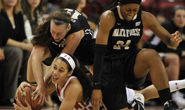 Wake Forest's Kelila Atkinson, right, and Millesa Calicott, behind, and Maryland's Chloe Pavlech, bottom, reach for a loose ball in the second half of an NCAA college basketball game on Thursday, Jan 9, 2014, in College Park, Md. Maryland won 76-49. (AP Photo/Gail Burton)