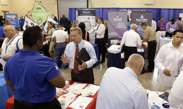 In this photo taken Wednesday, July 16, 2014, job seekers check out the job opportunities at a Hiring Fair For Veterans in Fort Lauderdale, Fla. Rising sales helped boost hiring and wages at U.S. businesses in the second quarter, and companies are optimistic that the trends will continue this fall, according to a new survey by the National Association for Business Economics. (AP Photo/Alan Diaz)