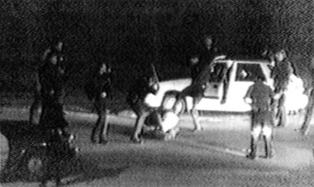 FILE - This March 31, 1991 frame from a video tape shot by George Holliday from his apartment in a suburb of Los Angeles shows what appears to be a group of police officers beating a man with nightsticks and kicking him as other officers look on. The April 29, 1992 acquittal of four police officers in the beating sparked rioting that spread across the city and into neighboring suburbs. Cars were demolished and homes and businesses were burned. Before order was restored, 55 people were dead, 2,300 injured and more than 1,500 buildings were damaged or destroyed.(AP Photo/George Holliday/Courtesy of KTLA Los Angeles)