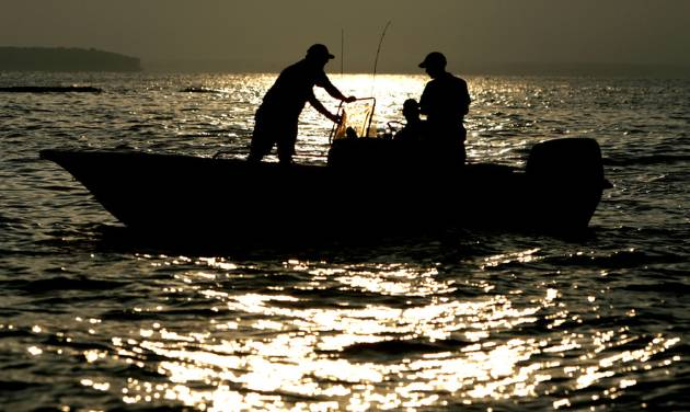 Striper anglers try their luck in the early morning hours as the sun rises over Lake Texoma. Photo by Bryan Terry, The Oklahoman Archive