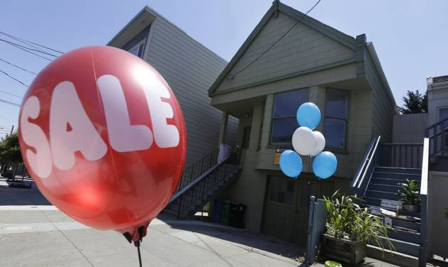 A sale balloon for a nearby store is shown next to a property in the Noe Valley neighborhood just sold for $1.8 million in cash, $600,000 more than its asking price, in San Francisco, Wednesday, July 30, 2014. In the souped-up world of San Francisco real estate, where the median selling price for homes and condominiums hit seven figures for the first time last month, the cool million that would fetch a mansion on a few acres elsewhere will now barely cover the cost of an 800-square-foot starter home. (AP Photo/Jeff Chiu)