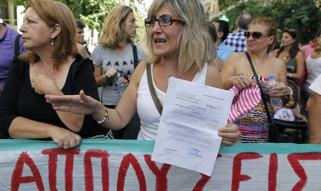 """Paraskevi Pappa, until this week employed at the Amalia Fleming state hospital, holds up a formal suspension order that places her on reduced pay pending dismissal or obligatory transfer to another state job, as she stands behind a banner which reads in Greek """" layoffs,"""" during a protest in Athens, on Thursday, Sept. 12, 2013. Doctors and medical staff from public hospitals gathered outside Greece's Health Ministry to protest mass public sector transfers and lay offs under the government's harsh austerity program. (AP Photo/Petros Giannakouris)"""