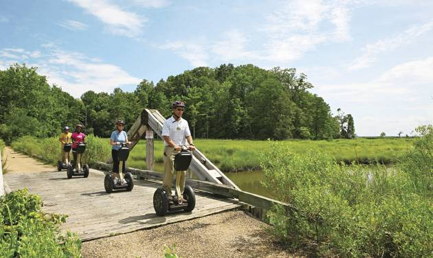 This July 2012 photo provided by Kingsmill Resort shows Kingsmill Resort's director of sports, Kevin Dry, leading a Segway tour on the resort's grounds in Williamsburg, Va. A number of hotels offer Segway tours as a novel way to see their grounds and nearby scenic areas. (AP Photo/Kingsmill Resort)