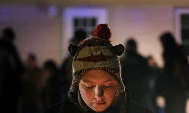 Micayla Weber, of Waterloo, Iowa, holds a candle during a vigil for missing cousins Lyric Cook, 10, and Elizabeth Collins, 8, who vanished while riding bikes in Evansdale in July, Thursday, Dec. 6, 2012, in Evansdale, Iowa. Authorities announced Thursday they are confident bodies found in an isolated wildlife area are those of the two girls. (AP Photo/Charlie Neibergall)