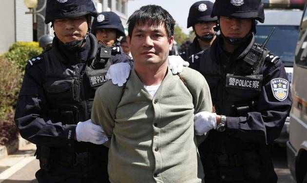 In this photo released by China's Xinhua News Agency, Myanmar drug lord Naw Kham, center, and three of his accomplices, unseen, are taken to the execution chambers where they will receive lethal injection in Kunming, capital of southwest China's Yunnan Province, Friday, March 1, 2013. China executed Naw Kham and the three accomplices Friday for the killing of 13 Chinese sailors in an attack on the Mekong River that spotlighted drug smuggling and extortion rackets along the vital waterway and led to a major expansion of Chinese police powers in a region that is coming under increasing domination by Beijing.  (AP Photo/Xinhua, Wang Shen) NO SALES