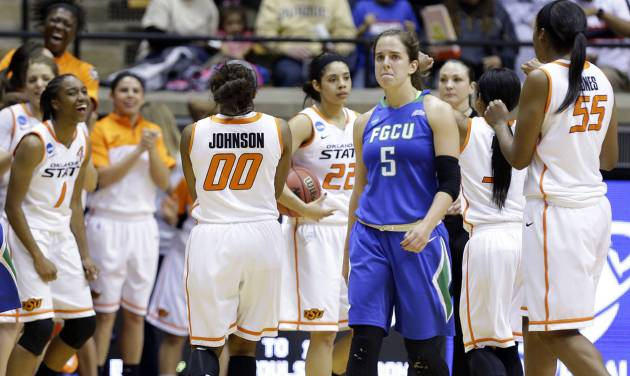 Florida Gulf Coast guard Sarah Hansen (5) walks off the court as Oklahoma State celebrates after winning 61-60 in overtime of a first-round game in the NCAA women's college basketball tournament in West Lafayette, Ind., Saturday, March 22, 2014.  (AP Photo/Michael Conroy)