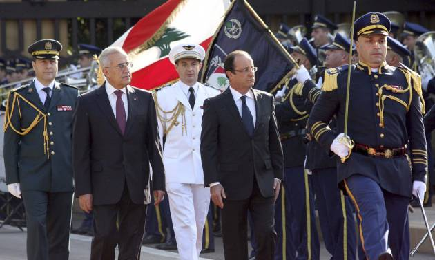 """In this photo released by Lebanon's official government photographer Dalati Nohra, Lebanese President Michel Suleiman, second left, and French President Francois Hollande, second right, review honor guards, at the Presidential Palace in Baabda, east of Beirut, Lebanon, Sunday, Nov. 4, 2012. Hollande said France will stand against instability in Lebanon. Hollande's comments during a short visit to Beirut come as many in Lebanon fear that Syria's civil war could spill over. Speaking to reporters after meeting President Michel Suleiman, Hollande said that amid Syria's civil war, """"we are committed to give you guarantees regarding security, stability and the unity of Lebanon."""" A top anti-Syrian intelligence chief was killed in a car bomb in Beirut last month. The assassination stirred up deadly sectarian tensions in Lebanon, where Sunnis and Shiites are deeply divided over the Syrian civil war, raising the specter of renewed sectarian fighting. (AP Photo/Dalati Nohra)"""