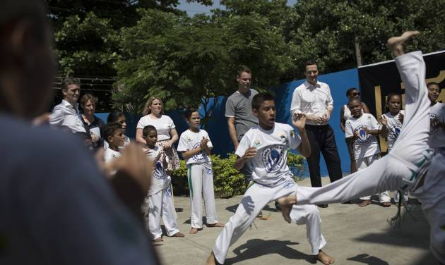 Britain's Chancellor of the Exchequer George Osborne, top right, watches youth who are part of the social project 'Luta Pela Paz,' or Fight for Peace, practice capoeira in the Mare slum complex in Rio de Janeiro, Brazil, Monday, April 7, 2014. More than 2,000 Brazilian Army soldiers moved into the Mare slum complex early Saturday in a bid to improve security and drive out the heavily armed drug gangs that have ruled the sprawling slum for decades. (AP Photo/Felipe Dana)