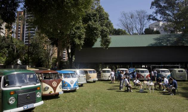 """In this Aug. 25, 2013 photo, members of the Sampa Kombi club, a group ofVolkswagen van owners, gather for their monthly meeting, in Sao Paulo, Brazil. In Brazil the VW van is known as the """"Kombi,"""" an abbreviation for the German """"Kombinationsfahrzeug"""" that loosely translates as """"cargo-passenger van."""" Brazil is the last place in the world still producing the iconic vehicle, or """"bus"""" as it's known by aficionados, but VW says production will end Dec. 31. Safety regulations mandate that every vehicle in Brazil must have air bags and automatic brakes starting in 2014, and the company says it cannot change production to meet the law. (AP Photo/Andre Penner)"""