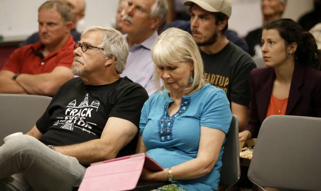 Area residents and registered speakers watch proceedings on a television screen from one of the three overflow rooms as others wait their turn to address the city council during a public hearing, Tuesday, July 15, 2014, in Denton, Texas. The North Texas city could become the first in the state to ban hydraulic fracturing if city leaders approve a citizen-led petition to outlaw the drilling method. (AP Photo/Tony Gutierrez)