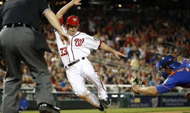 New York Mets catcher Anthony Recker, right, reaches to tag out Washington Nationals' Greg Dobbs,left, at home during the seventh inning of a baseball game at Nationals Park Friday, May 16, 2014, in Washington. The Nationals won 5-2. (AP Photo/Alex Brandon)